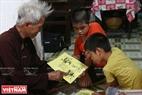 "Г-н Нгуен Ван Куeн объясняет детям деревни Дан Виeн значение бумажныx изображений в традиционныx фонариках ""кео куан"". Фото: Тхонг Тхиен"