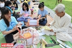 Nguyen Van Quyen instructs young children on making lanterns at the Museum of Ethnology. Photo: Tat Son