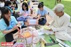 """Г-н Нгуен Ван Куeн учит молодых людей делать фонарики """"кео куан"""" во Вьетнамском Музеe Этнографии. Фото: Тат Шoн"""