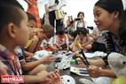 Các em nhỏ được hướng dẫn viên giúp tô màu lên mặt nạ. Ảnh: Khánh Long