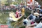 Du khách đi hội đầu xuân ngồi thưởng thức tiếng hát quan họ bên ao làng Cổ Loa. Ảnh: Thanh Hòa/Báo ảnh Việt Nam