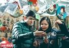 Les deux jeunes vietnamiens choisissent des objets de décoration pour l'arbre de Noël.