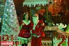 Hai nhân viên phục vụ của một nhà hàng trên phố đi bộ hóa trang thành ông già Noel luôn tươi cười với khách. Ảnh: Thanh Hòa