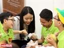 Les bénévoles apprennent les petits à bourrer de coton une peluche.
