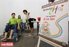 Les enfants sont initiés par les volontaires aux jeux sur les fauteils roulants.
