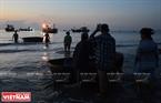 Những chiếc thúng bắt đầu rời bến ra đón những chuyến hàng đầy ắp cá tôm từ các tàu lớn vừa đánh bắt khơi xa về. Ảnh: Thanh Hòa