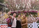 桜のそばで記念写真を撮影するハノイの人民立ち。