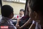 Các em học sinh vui vẻ chào đón nhau lên xe.