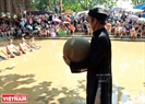 An older man carries the 20kg wooden ball from the temple to the field.