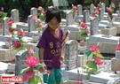 Giữa trưa hè oi ả, một cháu bé người Quảng Trị lặng lẽ đi dọc theo các hàng mộ để tưới lên đó những giọt nước trong lành mong làm mát lòng những người nằm xuống. Ảnh: Thanh Hoà