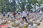 Các bạn trẻ người New Zealand chia nhau đi thắp hương lên các phần mộ liệt sĩ ở Nghĩa trang Liệt sĩ Quốc gia Trường Sơn. Ảnh: Thanh Hoà