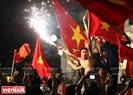 Болельщики празднуют подвиг футболистов страны у берега озера Возвращенного меча. Фото: Тат Шон.