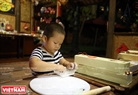 A little boy attentively kneads the dough to make a moon cake.