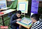 两名年轻人在民间游戏区下棋。