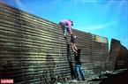 Những người di cư từ Trung Mỹ trèo lên hàng rao biên giới giữa Mexico và Hoa Kỳ vào ngày 25/11.