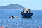 ダーデストーンビーチから大きな船へゴミを運ぶために、サーフボードを使用する。撮影:タイン・ホア
