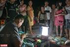 Một nghệ sĩ làm tranh cát thể hiện những tác phẩm về phong cảnh Phú Quốc ngay tại chợ. Ảnh: Lê Minh