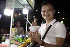 Du khách vui vẻ thưởng thức những món quà vặt ở Chợ đêm Phú Quốc. Ảnh: Kim Phương