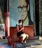 격리된 동네에서 거주하는 한 여성이 아침 햇살을 받으며 앉아 있다. 사진: 타잉화(Thanh Hòa)